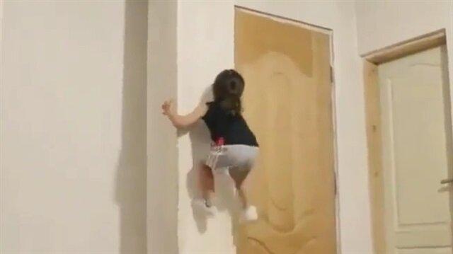 Düz duvara tırmanan küçük kız