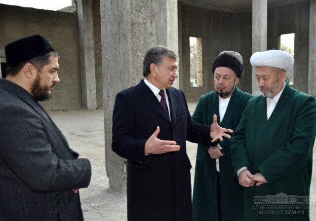 Cumhurbaşkanı Şevket Mirziyoyev Özbekistan Dini İdaresi Başkanı Osmanhan Alimov'la ( en sağda) 2015 yılında vefat eden eski Özbekistan Müftüsü Muhammed Sadık Muhammed Yusuf'un adını taşıyacak caminin yapılacağı mekanda konuşurken.