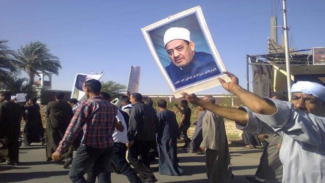 Göstericiler, Ahmed Tayyib'in posterlerini taşıdı.