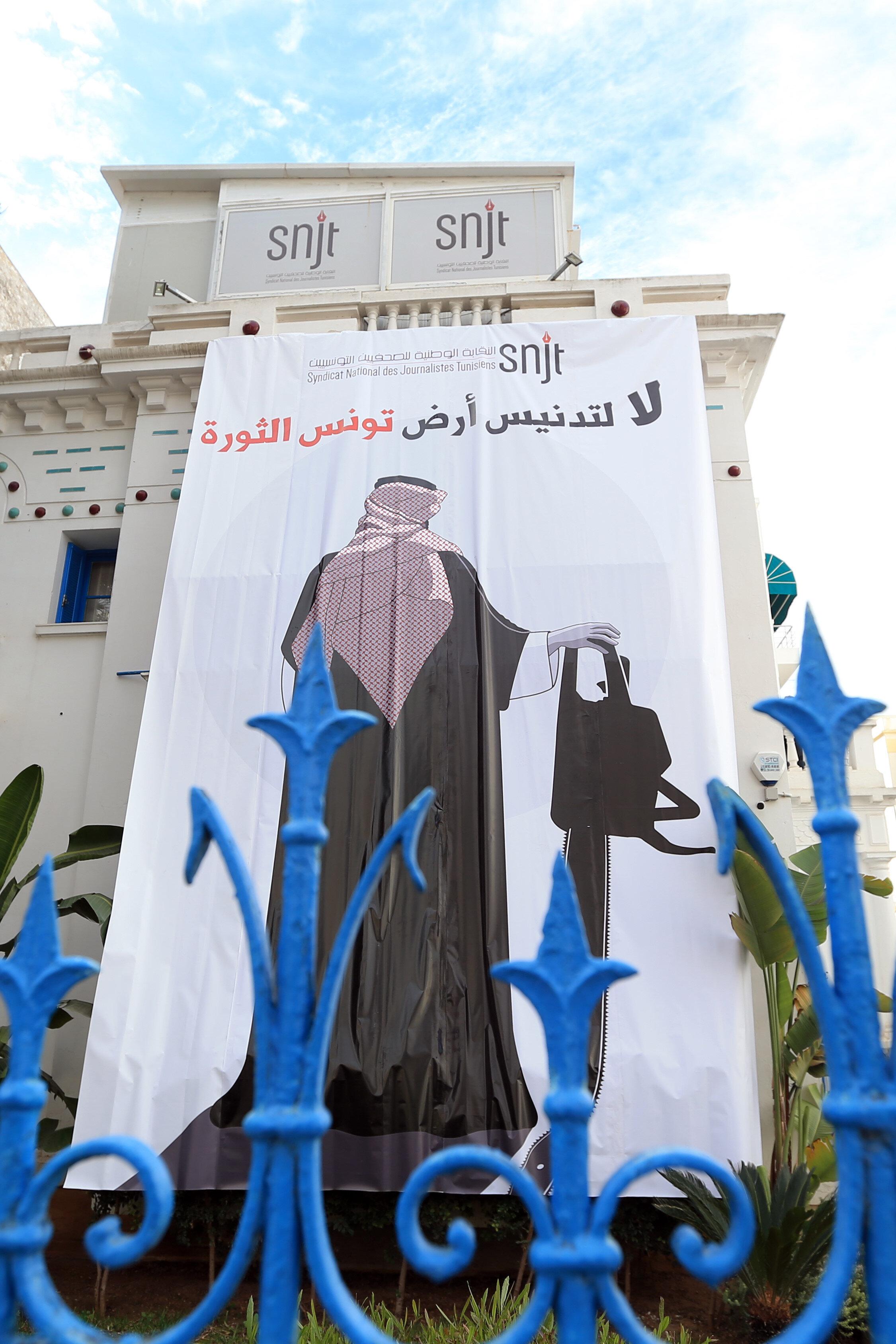 Tunuslular Bin Selman'ın elektrikli testereyle resm edildiği bir dev bir pankarta ''Devrim toprağı Tunus'un kirletilmesine, hayır'' diye yazdılar.