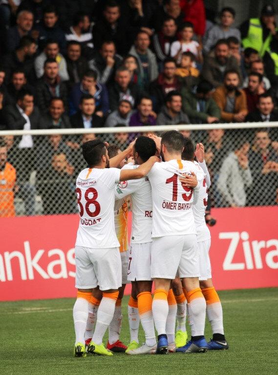 Galatasaray forması giyen genç oyuncular, golü kenetlenerek kutluyor.