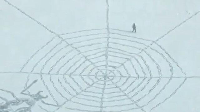 Karla kaplı arazide dev örümcek ağı çizen adam