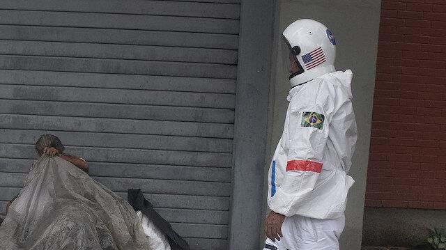 Brezilya'da bir kişi astronot kıyafetiyle koronavirüsten korunmaya çalışıyor